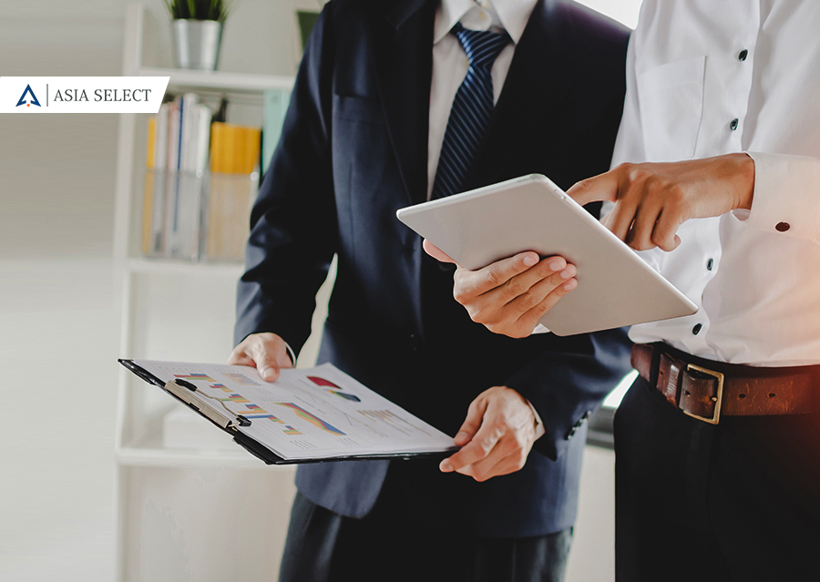 one man in professional attire pointing on an ipad and the other man in professional attire is interested with what is on the ipad